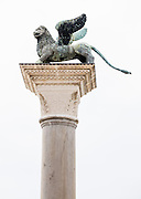 """A statue of the winged Lion of St. Mark, one of two patron saints of Venice, rises on a tall granite column erected in the 1200s in Piazzetta San Marco, in Venice, Veneto, Italy, Europe. The winged Lion of St. Mark, which appeared on the flag and coat of arms of the Republic of Venice, is still featured in the red-yellow flag of the city of Venice (with six tails, one for each sestiere of the city), in its coat of arms, and in the yellow-red-blue flag of the Veneto region (which has seven tails representing its seven provinces). The winged lion also appears in the naval ensign of the Italian Republic, alongside the coat of arms of three other medieval Italian maritime republics (Genoa, Pisa and Amalfi), as well as the Golden Lion, awarded at the Venice Film Festival. Venezia is the capital of Italy's Veneto region, named for the ancient Veneti people from the 900s BC. The romantic """"City of Canals"""" stretches across 100+ small islands in the marshy Venetian Lagoon along the Adriatic Sea between the mouths of the Po and Piave Rivers. The Republic of Venice was a major maritime power during the Middle Ages and Renaissance, a staging area for the Crusades, and a major center of art and commerce (silk, grain and spice trade) from the 1200s to 1600s. The wealthy legacy of Venice stands today in a rich architecture combining Gothic, Byzantine, and Arab styles."""