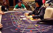 Gamblers play Baccarat in a casino, in Macao, China, on April 30, 2010. Photo by Juha-Pekka Kervinen/Pictobank