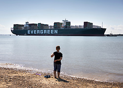 © Licensed to London News Pictures. 03/08/2021. Felixstowe, UK. A youty watches from the shore as the container ship 'Ever Given' arrives at the port of Felixstowe in Suffolk. The giant 400 metre long cargo ship became stuck in the Suez Canal in March causing worldwide delays to trade and was only released by the Egyptian authorities after an agreement was reached over a £655m compensation claim. Photo credit: Peter Macdiarmid/LNP