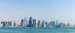 Panoramic view along waterfront of Corniche towards modern office towers in West Bay financial and business district in Doha Qatar