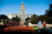 """SHOT 8/27/09 7:01:24 PM - Tourists take in Civic Center Park in the heart of Denver, Co. as the Colorado State Capitol rises in the background. The area is known as the center of the civic life in the city, with numerous institutions of arts, government, and culture as well as numerous festivals, parades, and protests throughout the year. The park is home to many fountains, statues, and formal gardens, and includes a Greek amphitheater, a war memorial, and the Voorhees Memorial Seal Pond. It is well known for its symmetrical Neoclassical design. Colfax Avenue is the main street that runs east and west through the Denver-Aurora metropolitan area in Colorado. As U.S. Highway 40, it was one of two principal highways serving Denver before the Interstate Highway System was constructed. In the local street system, it lies 15 blocks north of the zero point (Ellsworth Avenue, one block south of 1st Avenue). For that reason it would normally be known as """"15th Avenue"""" but the street was named for the 19th-century politician Schuyler Colfax. On the east it passes through the city of Aurora, then Denver, and on the west, through Lakewood and the southern part of Golden. Colloquially, the arterial is referred to simply as """"Colfax"""", a name that has become associated with prostitution, crime, and a dense concentration of liquor stores and inexpensive bars. Playboy magazine once called Colfax """"the longest, wickedest street in America."""" However, such activities are actually isolated to short stretches of the 26-mile (42 km) length of the street. Periodically, Colfax undergoes redevelopment by the municipalities along its course that bring in new housing, trendy businesses and restaurants. Some say that these new developments detract from the character of Colfax, while others worry that they cause gentrification and bring increased traffic to the area. (Photo by Marc Piscotty / © 2009)"""