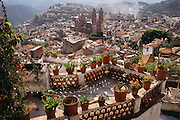 View of Taxco, a colonial silver mining hill town in Mexico, with a patio in the foreground.
