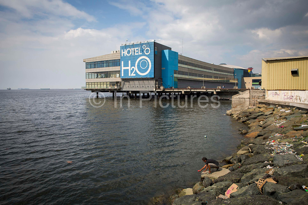 A man fishing in the south harbour of Manila Bay in front of Hotel H2O in Luneta, Manila, Metro Manila, Philippines. The Hotel H2O is part of Manila Ocean Park and supports some life-sized fish tanks.