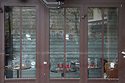 Bullet holes and blood on window panes. Cafe Bonne Biere, Rue Fontaine au Roi, near Republique<br /><br />The Day after the terrorist jihadi attacks. Bullet holes and blood, mourning homage and cleaning up. Aftermath of deadly Paris terrorist attacks. Saturday 14th November 2015<br /> <br /> Eight terrorists dead and some 128 people killed at Stade de France, Bataclan concert Hall, Belle Equipe Restaiurant, Rue Fontaine au Roi, Two hundred people have been injured, 80 of them seriously.