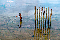 July 1987, Biak Island, Schouten Islands, Indonesia --- A naked young boy fishes with a pointed stick near a row of wooden pilings. Biak Island, Schouten Islands, Indonesia