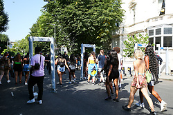 © Licensed to London News Pictures. 26/08/2019. London, UK. People walk thorough the security scanners as over a million people attend the 2019 Notting Hill Carnival, Europe's largest street party and a celebration of Caribbean traditions and the capital's cultural diversity. Photo credit: Dinendra Haria/LNP