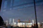 The Victorian Tower Bridge and the Tower of London (below)  is seen reflected in the large glass windows of a nearby restaurant in the borough of Southwark.