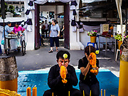 """11 APRIL 2017 - BANGKOK, THAILAND: A man prays at Wat Chana Songkhram in Bangkok during a Songkran merit making service. Songkran is the traditional Thai Lunar New Year. It is celebrated, under different names, in Thailand, Myanmar, Laos, Cambodia and some parts of Vietnam and China. In most places the holiday is marked by water throwing and water fights and it is sometimes called the """"water festival."""" This year's Songkran celebration in Thailand will be more subdued than usual because Thais are still mourning the October 2016 death of their revered Late King, Bhumibol Adulyadej. Songkran is officially a three day holiday, April 13-15, but is frequently celebrated for a full week. Thais start traveling back to their home provinces over the weekend; busses and trains going out of town have been packed.     PHOTO BY JACK KURTZ"""