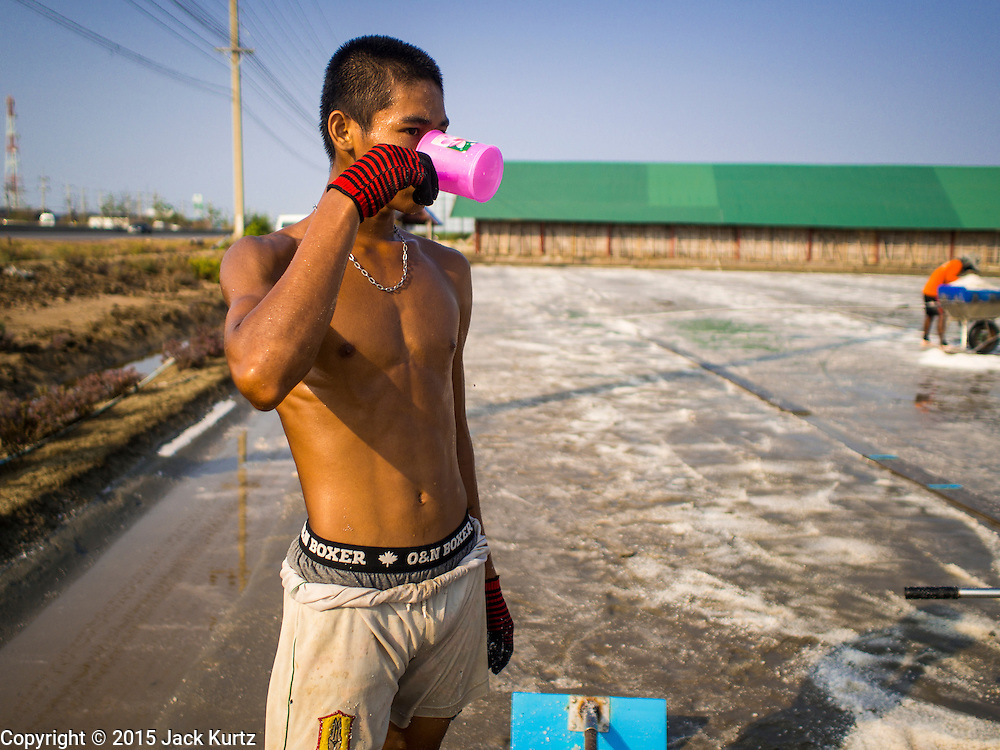 09 MARCH 2015 - NA KHOK, SAMUT SAKHON, THAILAND: A Burmese migrant worker on a salt farm near Samut Sakhon, Thailand, drinks a cup of water during the salt harvest. The coastal provinces of Samut Sakhon and Samut Songkhram, about 60 miles from Bangkok, are the center of Thailand's sea salt industry. Salt farmers harvest salt from the waters of the Gulf of Siam by flooding fields and then letting them dry through evaporation, leaving a crust of salt behind. Salt is harvested through dry season, usually February to April. The 2014 salt harvest went well into May because the dry season lasted longer than normal. Last year's harvest resulted in a surplus of salt, driving prices down. Some warehouses are still storing salt from last year. It's been very dry so far this year and the 2015 harvest is running ahead of last year's bumper crop. One salt farmer said prices are down about 15 percent from last year.    PHOTO BY JACK KURTZ