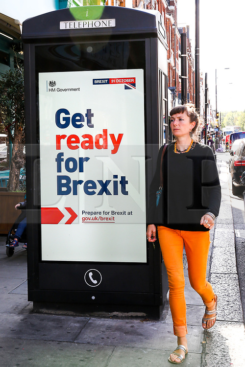 """© Licensed to London News Pictures. 02/09/2019. London, UK. A woman walks past a """"Get ready for Brexit"""" digital advert on the back of a telephone box in north London.<br /> Today the UK Government launches a £100-million no-deal public information campaign with the slogan """"Get ready for Brexit"""" as MPs attempt to delay Brexit. The campaign is hailed as the biggest government advertising drive since the Second World War. It is meant to ensure that businesses and the public are prepared in case Britain departs the EU without an agreement on October 31.<br /> Photo credit: Dinendra Haria/LNP"""