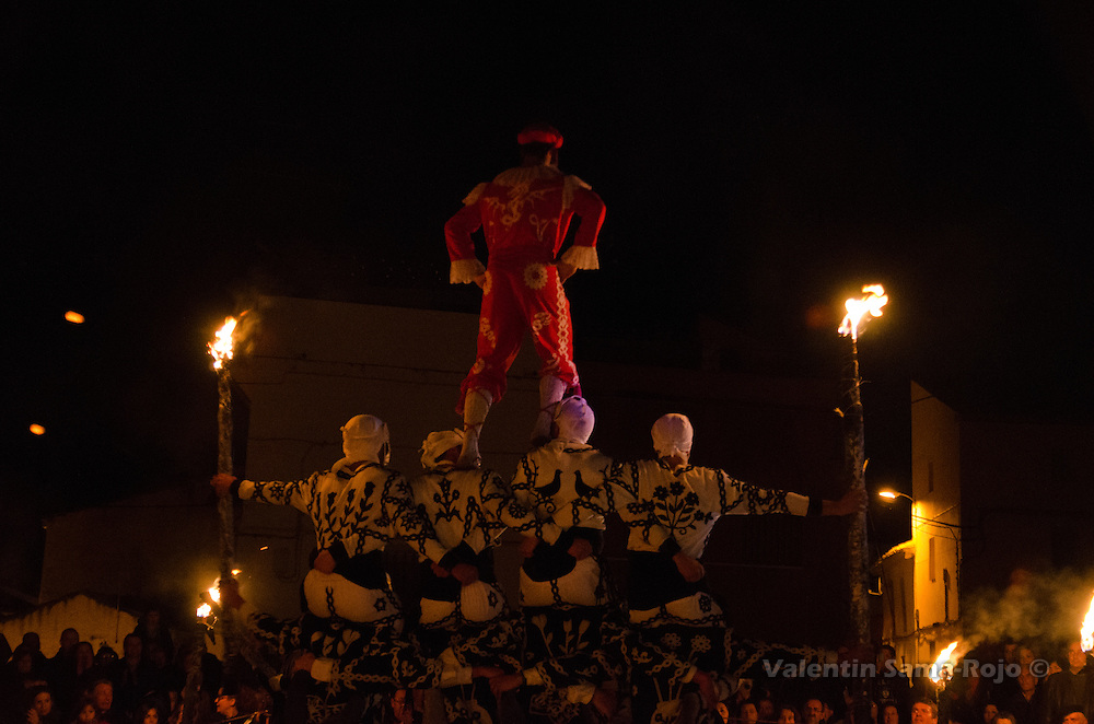 Backwards view of the 'Contradanceros' performing the tower as an altarpiece with the Devil on top and burning torches on each side.