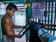 """31 MARCH 2017 - BANGKOK, THAILAND: A worker hangs dyed silk threads to dry in a home in the Ban Krua neighborhood in Bangkok. The Ban Krua neighborhood of Bangkok is the oldest Muslim community in Bangkok. Ban Krua was originally settled by Cham Muslims from Cambodia and Vietnam who fought on the side of the Thai King Rama I. They were given a royal grant of land east of what was then the Thai capitol at the end of the 18th century in return for their military service. The Cham Muslims were originally weavers and what is known as """"Thai Silk"""" was developed by the people in Ban Krua. Several families in the neighborhood still weave in their homes.                    PHOTO BY JACK KURTZ"""