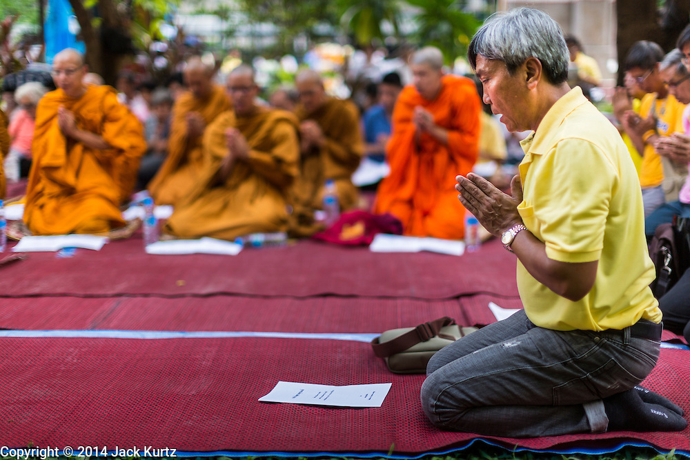 09 OCTOBER 2014 - BANGKOK, THAILAND: A man wearing yellow prays for Bhumibol Adulyadej, the King of Thailand, during a prayer service led by Buddhist monks on the plaza in front of Siriraj Hospital. People wear yellow when they pray for the King because it's the King's color. The King has been hospitalized at Siriraj Hospital since Oct. 4 and underwent emergency gall bladder removal surgery Oct. 5. The King is also known as Rama IX, because he is the ninth monarch of the Chakri Dynasty. He has reigned since June 9, 1946 and is the world's longest-serving current head of state and the longest-reigning monarch in Thai history, serving for more than 68 years. He is revered by the Thai people and anytime he goes into the hospital thousands of people come to the hospital to sign get well cards.   PHOTO BY JACK KURTZ