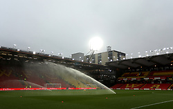 The pitch is watered at Vicarage Road before the match