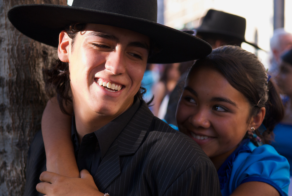 A couple of young dancers take a break from dancing on the downtown plaza in Santiago, Chile.