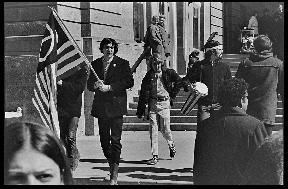 Madison, WI - March 1970. On March 15, 1970, the University of Wisconsin - Madison Teaching Assistants' Association voted to strike, and the campus was filled with picket lines as well as demonstrations of related and other issues. The strike lasted until early April, when the Association and University came to an agreement. A man carries a peace flag.