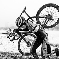 A Cyclocross riders carries his bike up a hill during a snowstorm at the Illinois Cyclocross Championships in Chicago