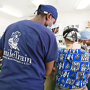 CAPTION: Dr Caouette-Laberge from Montreal discusses various possible techniques for cleft repair with the Haitian team and helps them to identify the one that will best suit the patient. LOCATION: Hôpital Universitaire Justinien, Cap-Haïtien, Haiti. INDIVIDUAL(S) PHOTOGRAPHED: Charles Lafontant (dark blue) and Dr Louise Caouette-Laberge (lead surgeon, centre).