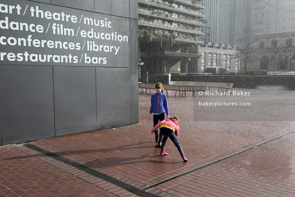 Young girls brave a spring downpour of rain, on 5th March 2017, at the Barbican in the City of London, England.
