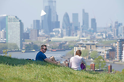 ©Licensed to London News Pictures 22/04/2020  <br /> Greenwich, UK. A couple enjoy a picnic with a London view. People out and about in Greenwich park, Greenwich, London exercising and enjoying the warm sunny weather. Photo credit:Grant Falvey/LNP