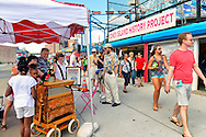 Brooklyn, New York, USA. 10th August 2013. The Coney Island History Project banner is over the booth where visitors can get information about the world famous neighborhood, beach and boardwalk and amusement park, during the 3rd Annual Coney Island History Day celebration. A Wonder Wheel sign points to the entrance to the famous ride.