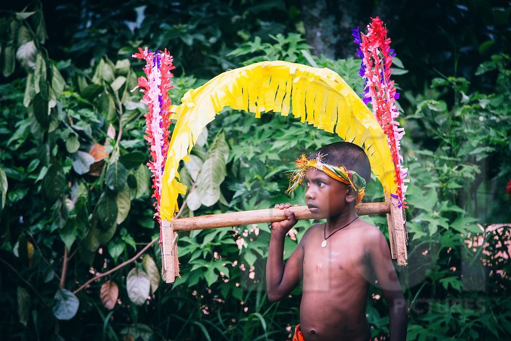 A young kid holds an offer during a traditional religious ritual in the area of Adam's Peak, Sri Lanka, Asia