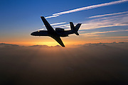 Cessna Citation Excel (XL) business jet flying at sunset over the clouds.