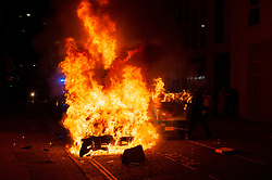 """© Licensed to London News Pictures;21/03/2021; Bristol, UK. A police van is set on fire as police clash with protesters outside New Bridewell Police Station on Sunday evening during a """"Kill the Bill"""" protest against Police, Crime, Sentencing and Courts Bill takes place through the centre of Bristol during the Covid-19 coronavirus pandemic in England. The Bill proposes new restrictions on protests. Lockdown restrictions have been partly lifted to allow people to gather outdoors socially in households, bubbles, or to meet one person from another household, but the police say protests are not allowed under the current Covid regulations. Photo credit: Simon Chapman/LNP."""