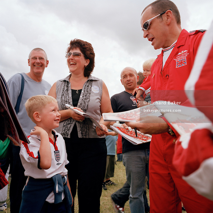 Squadron Leader Spike Jepson of the Red Arrows, Britain's RAF aerobatic team signs publicity brochures for boy during airshow.