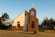 A small church on the island of Kauai with a stone steeple and white cross.