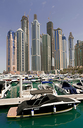 Boats and high rise apartment towers at Dubai Marina in Dubai United Arab Emirates UAE
