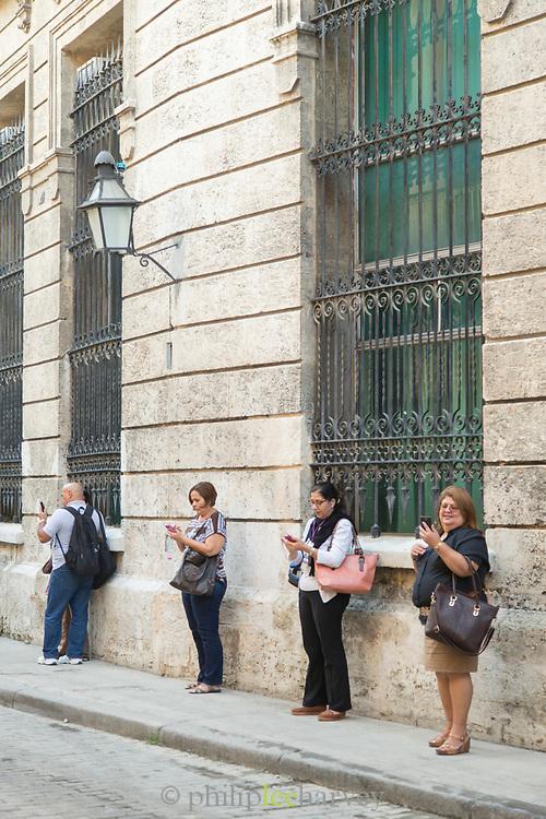 Four people using phones standing on sidewalk, Havana, Cuba