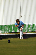 Woman delivering wood on a Lawn bowling green. Model released