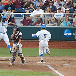 Jun 25, 2013; Omaha, NE, USA; UCLA Bruins designated hitter Kevin Williams (5) scores against Mississippi State Bulldogs catcher Nick Ammirati (center) during the fourth inning in game 2 of the College World Series finals at TD Ameritrade Park. Mandatory Credit: Derick E. Hingle-USA TODAY Sports