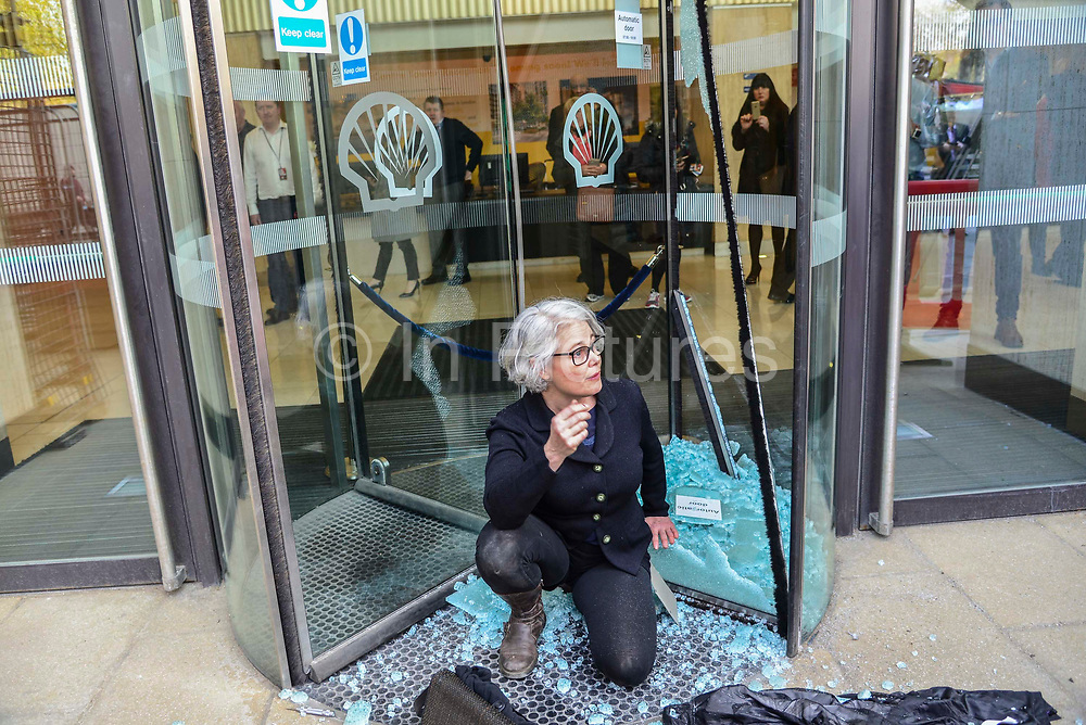 A woman sits amongst broken glass after smashing a glass door with a screw driver at the Shell oil HQ on 15th April 2019 in London, United Kingdom.  Extinction Rebellion a climate change protest group are protesting  across the centre of London and plan to block traffic for the next five days.
