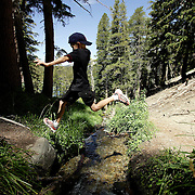 MAMMOTH, CA, AUG 22, 2006:  A young boy leaps over Coldwater Canyon Creek while hiking in Mammoth, California  on August 22, 2006  (Photograph by Todd Bigelow/Aurora).