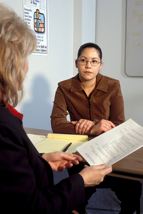 Hispanic woman (21) exhibiting uneasiness, shyness during job interview by Anglo woman. ©Bob Daemmrich/