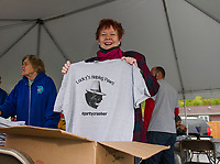 Patty Johnson hands out Lucky's Helping Paws t-shirts at Sanborn's Auto during Lucky Jr's birthday party on Saturday.  (Karen Bobotas/for the Laconia Daily Sun)