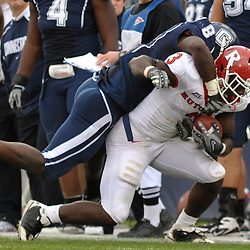 Oct 31, 2009; East Hartford, CT, USA; Connecticut linebacker Lawrence Wilson (8) tackles Rutgers tight end Shamar Graves (3) after  a reception during second half Big East NCAA football action in Rutgers' 28-24 victory over Connecticut at Rentschler Field.