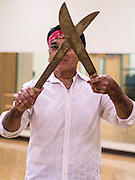 27 JUNE 2012 - GLENDALE, AZ:   HENRY ARBALLO dances with machetes during rehearsal for the Senior Fiesta Dancers at the Glendale Adult Center, in Glendale, AZ, a suburb of Phoenix. Dancing as a part of workout regimen is not unusual, but the Senior Fiesta Dancers use Mexican style folklorico dances for their workouts. The Senior Fiesta Dancers have been performing together for 15 years. They get together every week for rehearsals and perform at nursing homes and retirement centers in the Phoenix area once a month or so. Their energetic Mexican folklorico dances keep them limber and provide a cardio workout.  PHOTO BY JACK KURTZ