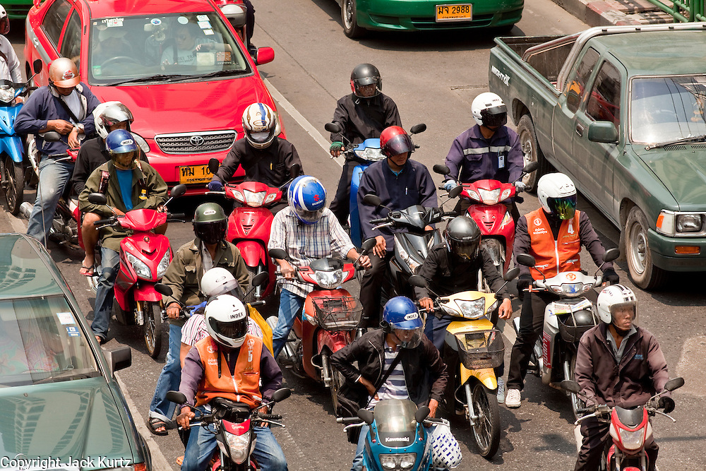 Mar 31, 2010 - BANGKOK, THAILAND: Motor scooters take off at an intersection in Bangkok, Thailand. Bangkok residents in 2007 produced as much carbon dioxide as New Yorkers and surpassed Londoners' emissions by 1.2 tons per capita, according to a United Nations sponsored report. Residents in Bangkok and New York each emitted 7.1 tons of the greenhouse gas in 2007 while London residents emitted 5.9 tons, according to a report compiled by the Bangkok government and the Green Leaf Foundation, a Bangkok-based environmental group, with support from the United Nations. Bangkok's transportation, electricity generation and solid wastewater treatment produced 90 per cent of the Thai capital's carbon dioxide with the transport sector alone accounting for almost 38 per cent of the annual total, the report said.   PHOTO BY JACK KURTZ