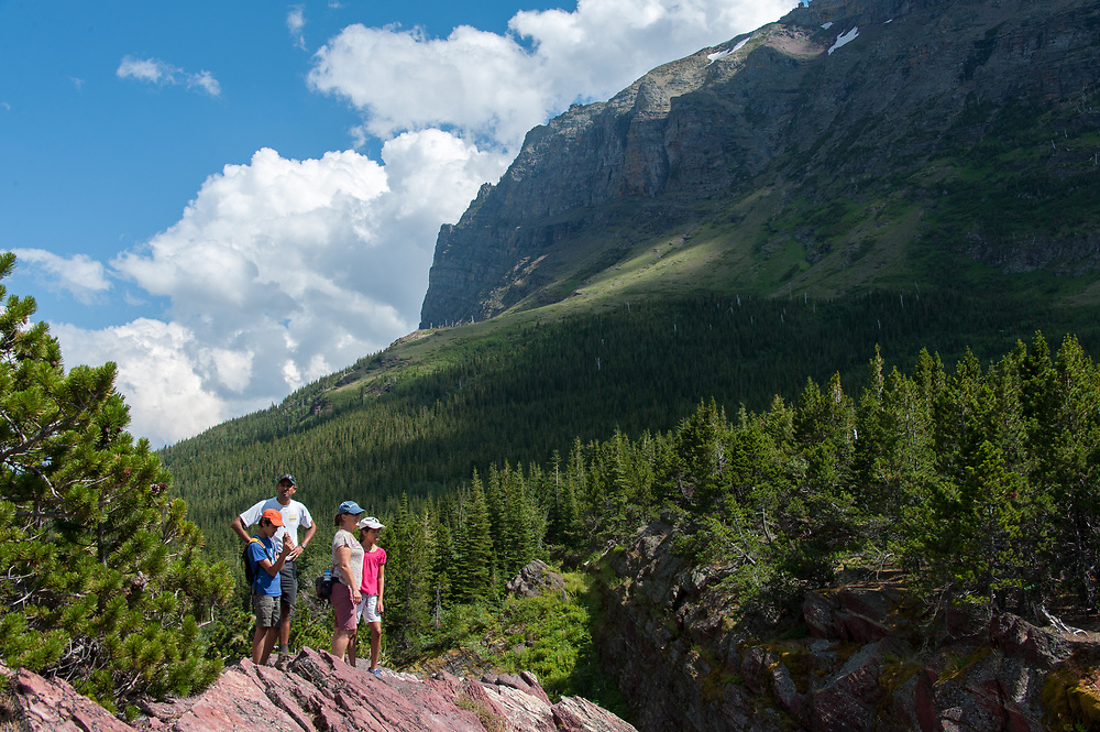 A family taking in the view on the Continental Divide Trail in Glacier National Park