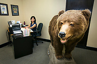 Josephine Coronel, property manager at Cusumano Real Estate Group, works beside the bear mascot of the office in  Burbank, CA. Feb. 5, 2014. Photo by David Sprague