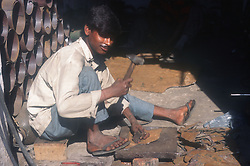 Metal work shop in the Punjab; India; with worker using hammer,
