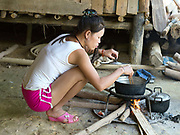 A Vietnamese prostitute prepares lunch at home in Ban Pakpok, Phongsaly province, Lao PDR. Ban Pakpok is small collection of houses recently relocated near to the Nam Ou river due to the Nam Ou Cascade Hydropower Project Dam 5. It is the closest habitation to the dam construction site, the local people rent rooms to the prostitutes who provide services to the Chinese construction workers.
