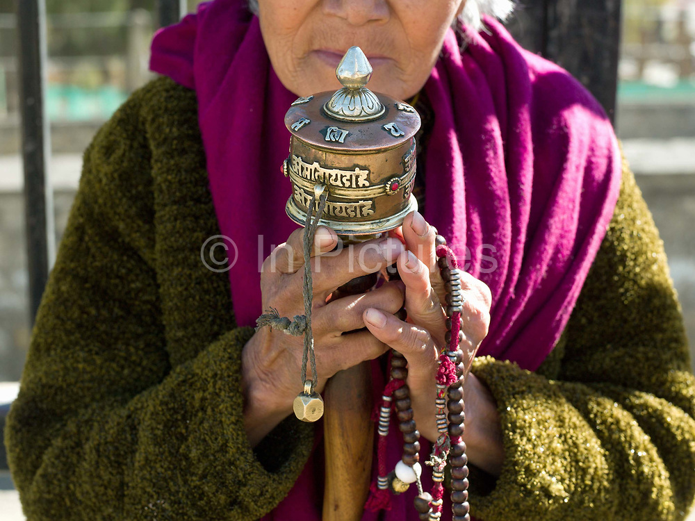 A Bhutanese woman holding a prayer wheel and rosary beads praying at the National Memorial Chorten in Thimphu, Western Bhutan. This large Tibetan-style chorten is one of the most visible religious structures in Thimphu and for many Bhutanese it is the focus of their daily worship. It was built in 1974 as a memorial to the third king, Jigme Dorji Wangchuck. Throughout the day people circumambulate the chorten, whirl the large red prayer wheels and pray at a small shrine inside the gate.