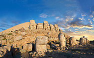 Statue heads at sunset, from left,  Eagle, Antiochus, Commagene, Zeus, Apollo, & Herekles with headless seated statues in front of the stone pyramid 62 BC Royal Tomb of King Antiochus I Theos of Commagene, east Terrace, Mount Nemrut or Nemrud Dagi summit, near Adıyaman, Turkey .<br /> <br /> If you prefer to buy from our ALAMY PHOTO LIBRARY  Collection visit : https://www.alamy.com/portfolio/paul-williams-funkystock/nemrutdagiancientstatues-turkey.html<br /> <br /> Visit our CLASSICAL WORLD HISTORIC SITES PHOTO COLLECTIONS for more photos to download or buy as wall art prints https://funkystock.photoshelter.com/gallery-collection/Classical-Era-Historic-Sites-Archaeological-Sites-Pictures-Images/C0000g4bSGiDL9rw