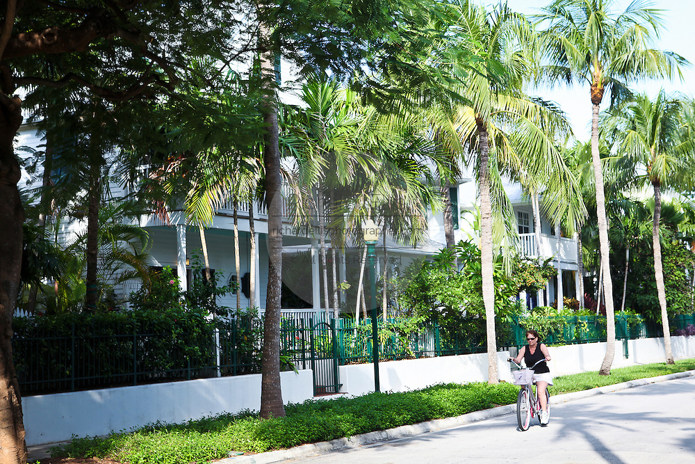 A bicyclist rides past Key West style homes in Key West, Florida