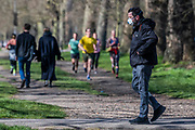 Joggers mix with walkers - People get out on Clapham Common to get their days exercise in - most practice social distancing but it is almost as busy as a normal spring day. The first day of the 'lockdown' in Clapham - Anti Coronavirus (Covid 19) outbreak in London.