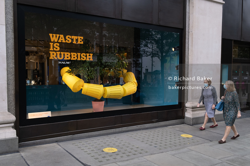 Two women wearing facial coverings walk past the latest window of Selfridges featuring a theme about plastic waste, on 26th August 2020, in London, England. Selfridges' latest green theme is called 'Project Earth', a 'transformational' sustainability initiative with ambitions to change the way consumers shop, helping to reduce waste, choose 'forest friendly' products and chose recycled or 'pre-loved' products.
